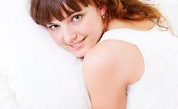 Junge hübsche Frau, die auf Kissen liegt Stockbilder