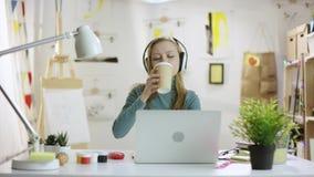 Junge hübsche Frau, die auf Musik und trinkenden Kaffee beim Sitzen durch Tabelle und Arbeiten an Laptop hört stock video