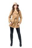 Junge hübsche Frau, die beige Mantel und den Hut aufwirft mit den Händen in den Taschen trägt lizenzfreie stockfotos
