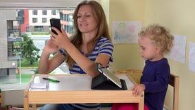 Junge hübsche Frau, die Fotos ihrer Tochter und selbst mit intelligentem Telefon macht stock video