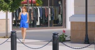 Junge hübsche Frau, die hinunter die Einkaufsstraße geht stock video
