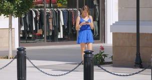 Junge hübsche Frau, die hinunter die Einkaufsstraße geht stock video footage