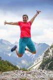 Junge hübsche Frau, die hoch in Glück, in den Bergen springt lizenzfreies stockfoto