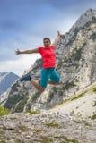 Junge hübsche Frau, die hoch in Glück, in den Bergen springt stockfotos