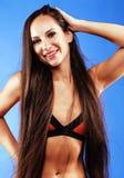 Junge hübsche Frau, die im Bikini auf blauem Hintergrund, Atelieraufnahme aufwirft heißer sportlicher Brunette Stockfotografie