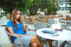 Junge hübsche Frau, die im Café im Freien sich entspannt und smartp verwendet Stockfotografie
