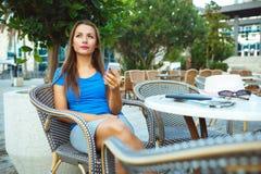 Junge hübsche Frau, die im Café im Freien sich entspannt und smartp verwendet Lizenzfreie Stockfotografie