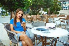 Junge hübsche Frau, die im Café im Freien sich entspannt und smartp verwendet Stockfoto