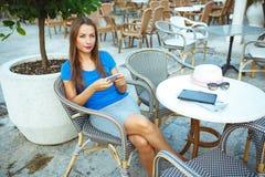 Junge hübsche Frau, die im Café im Freien sich entspannt und smartp verwendet Stockbilder