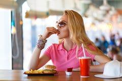 Junge hübsche Frau, die im Café stillsteht Stockfotografie