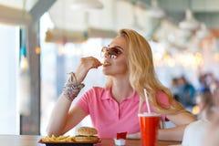 Junge hübsche Frau, die im Café stillsteht Lizenzfreies Stockbild