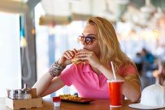 Junge hübsche Frau, die im Café stillsteht Stockfotos
