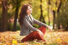 Junge hübsche Frau, die im Herbstpark sich entspannt stockfoto