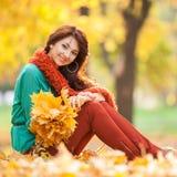 Junge hübsche Frau, die im Herbstpark sich entspannt lizenzfreie stockfotos
