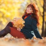 Junge hübsche Frau, die im Herbstpark sich entspannt lizenzfreies stockbild