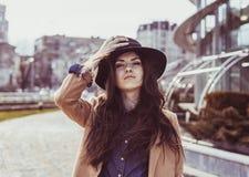 Junge hübsche Frau, die im Hut am Stadtzentrum aufwirft Stockbilder