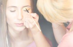 Junge hübsche Frau, die Make-up mit Pinsel erhält. Lizenzfreie Stockbilder