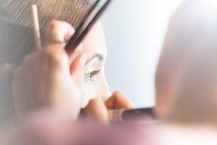 Junge hübsche Frau, die Make-up mit Pinsel erhält. Stockfoto