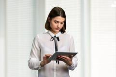 Junge hübsche Frau, die an PC-Tablette arbeitet lizenzfreie stockbilder