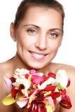 Junge hübsche Frau, die rosafarbene Blumenblätter anhält Stockfoto