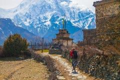 Junge hübsche Frau, die rote Jacken-Weitwanderweg-Berge trägt Gebirgstrekking schaukelt Weg-Dorf Schnee-Landschaftsansicht Lizenzfreies Stockbild