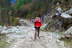 Junge hübsche Frau, die rote Jacken-Weitwanderweg-Berge trägt Gebirgstrekking schaukelt Weg-Landschaftsansicht-Hintergrund Stockfotografie