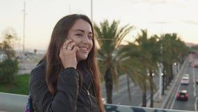 Junge hübsche Frau, die am Telefon auf einer Stadtbrücke spricht stock footage