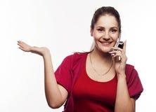 Junge hübsche Frau, die am Telefon spricht Lizenzfreie Stockfotografie