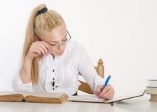 Junge hübsche Frau, die am Tisch erlernt Lizenzfreie Stockbilder