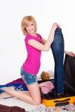 Junge hübsche Frau, die vorher ihren Koffer verpackt Lizenzfreies Stockbild