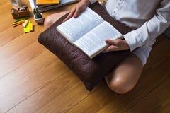 Junge hübsche Frau, die zu Hause sitzt, ein Buch lesend Lizenzfreies Stockfoto