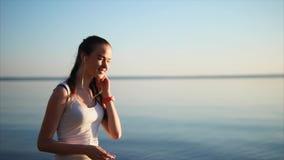 Junge hübsche Frau hören Musik unter Verwendung Kopfhörer stock footage