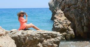 Junge hübsche Frau im Badeanzug und in Vertuschung, die auf den Felsen nahe dem Meer sitzen stock video