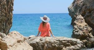 Junge hübsche Frau im Badeanzug und in Vertuschung, die auf den Felsen nahe dem Meer sitzen stock video footage