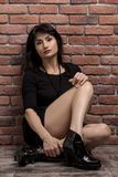 Junge hübsche Frau im dunklen kurzen Kleid nahe Backsteinmauer Stockbilder