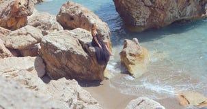 Junge hübsche Frau im eleganten Kleid des schwarzen Ausschnitts, das nahe dem Meer sitzt stock video