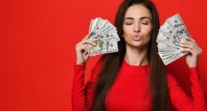 Junge hübsche Frau im roten Kleid, das hinter Bündel Geldbanknoten sich versteckt stockfotografie