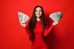 Junge hübsche Frau im roten Kleid, das hinter Bündel Geldbanknoten sich versteckt stockfoto