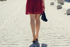 Junge hübsche Frau im roten Kleid gehend in die Stadt ohne Schuh stockbild