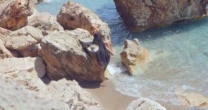 Junge hübsche Frau im schwarzen eleganten Kleid, das auf den Felsen nahe dem Meer sitzt stock video footage