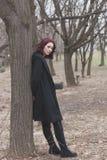 Junge hübsche Frau Mageren des schwarzen Mantels im im Freien auf Baum Körperschuss-Winterherbst des Parks im vollen stockfoto