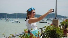 Junge hübsche Frau mit Blume in ihrem Haar, das selfie nimmt, stellen im Urlaub dar Stockbild