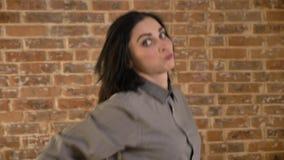 Junge hübsche Frau mit dem kurzen braunen Haar, das für Kamera aufwirft und lustige Gesichter, Backsteinmauerhintergrund tut stock footage