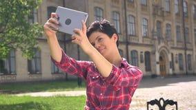 Junge hübsche Frau mit dem kurzen schwarzen Haar, das selfie mit der Tabelle, stehend auf Straße nahe College, sonniges Wetter ni stock footage
