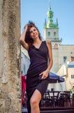 Junge hübsche Frau mit dem langen gelockten Haar, schlendernd unter der alten Stadt von Lemberg-Architektur im sexy schwarzen Kle Lizenzfreies Stockbild