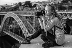 Junge hübsche Frau mit dem photocamera, das auf dem Standpunkt vor dem Duero-Fluss und der Brücke Dom Luis I in Porto, Hafen sitz Stockfotografie
