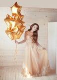 Junge hübsche Frau mit goldenem Stern steigt über hölzerner Beige b im Ballon auf Lizenzfreies Stockbild