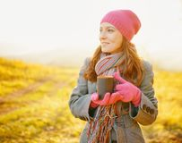 Junge hübsche Frau mit Kaffeetasse in den Händen Herbstsaison genießend lizenzfreie stockfotos