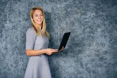Junge hübsche Frau mit Laptop über grauem Hintergrund Lizenzfreie Stockbilder