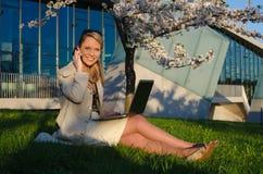 Junge hübsche Frau mit Unterhaltungshandy des Laptops Lizenzfreies Stockfoto